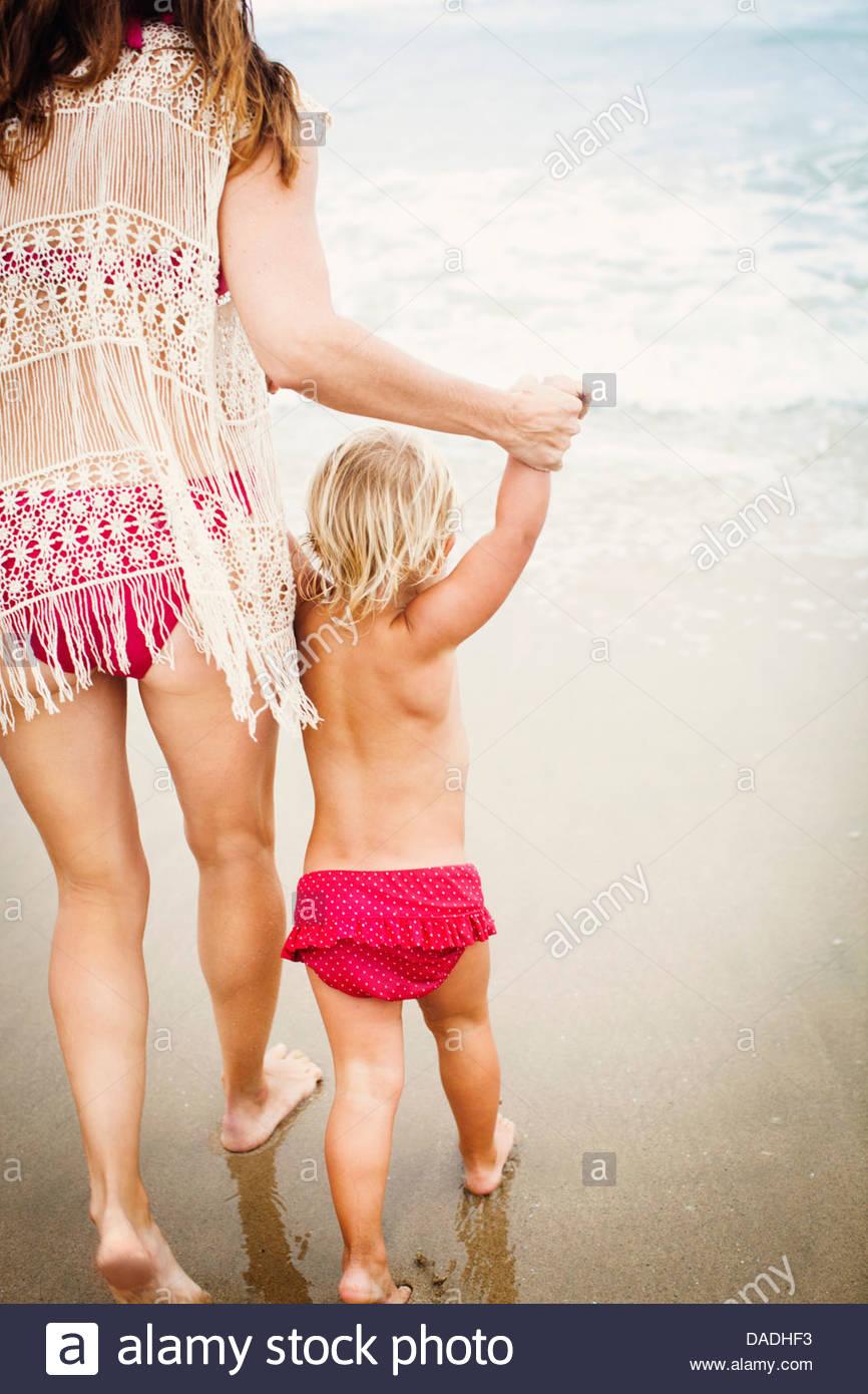 Vista posterior de la madre del niño líder en la playa Imagen De Stock