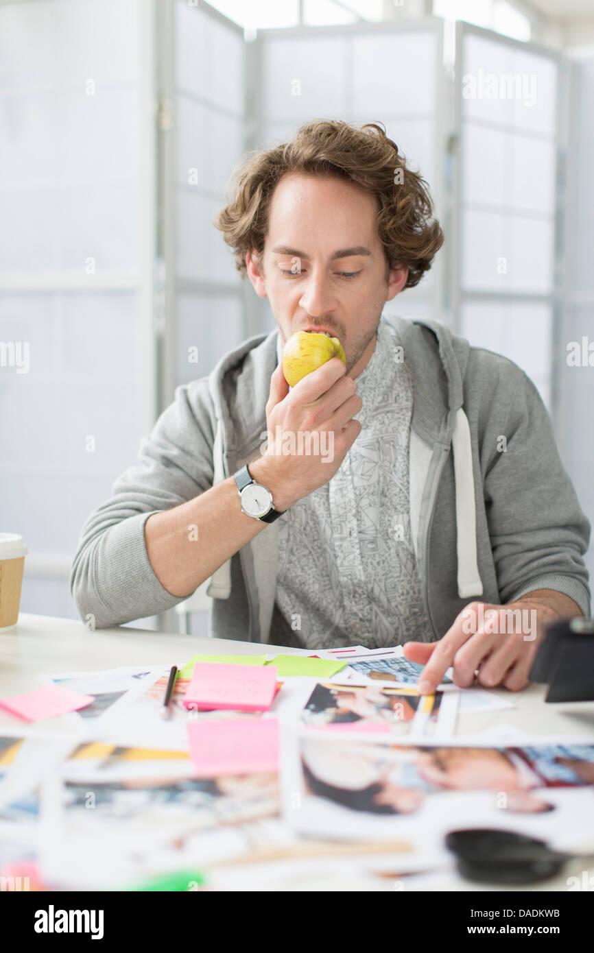 Joven comiendo apple en un escritorio en la oficina creativa Imagen De Stock