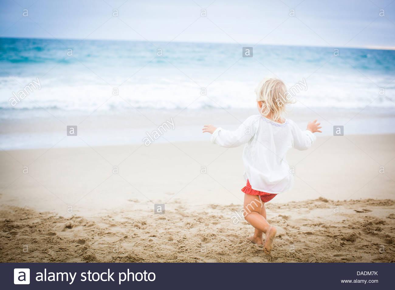 Vista posterior de la niña corriendo hacia el mar Imagen De Stock
