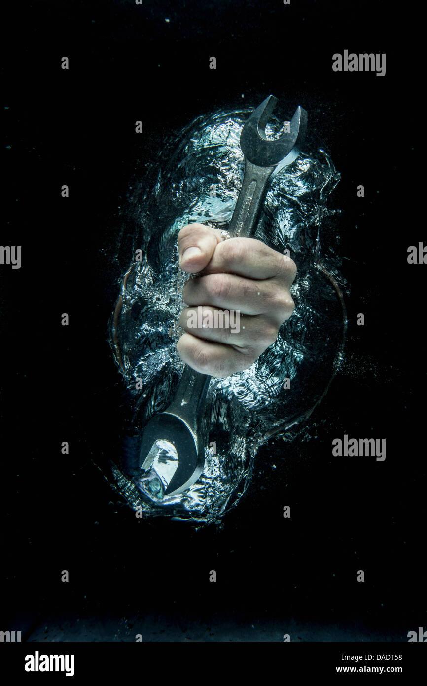 Hombre Mano agarrando la llave bajo el agua Imagen De Stock