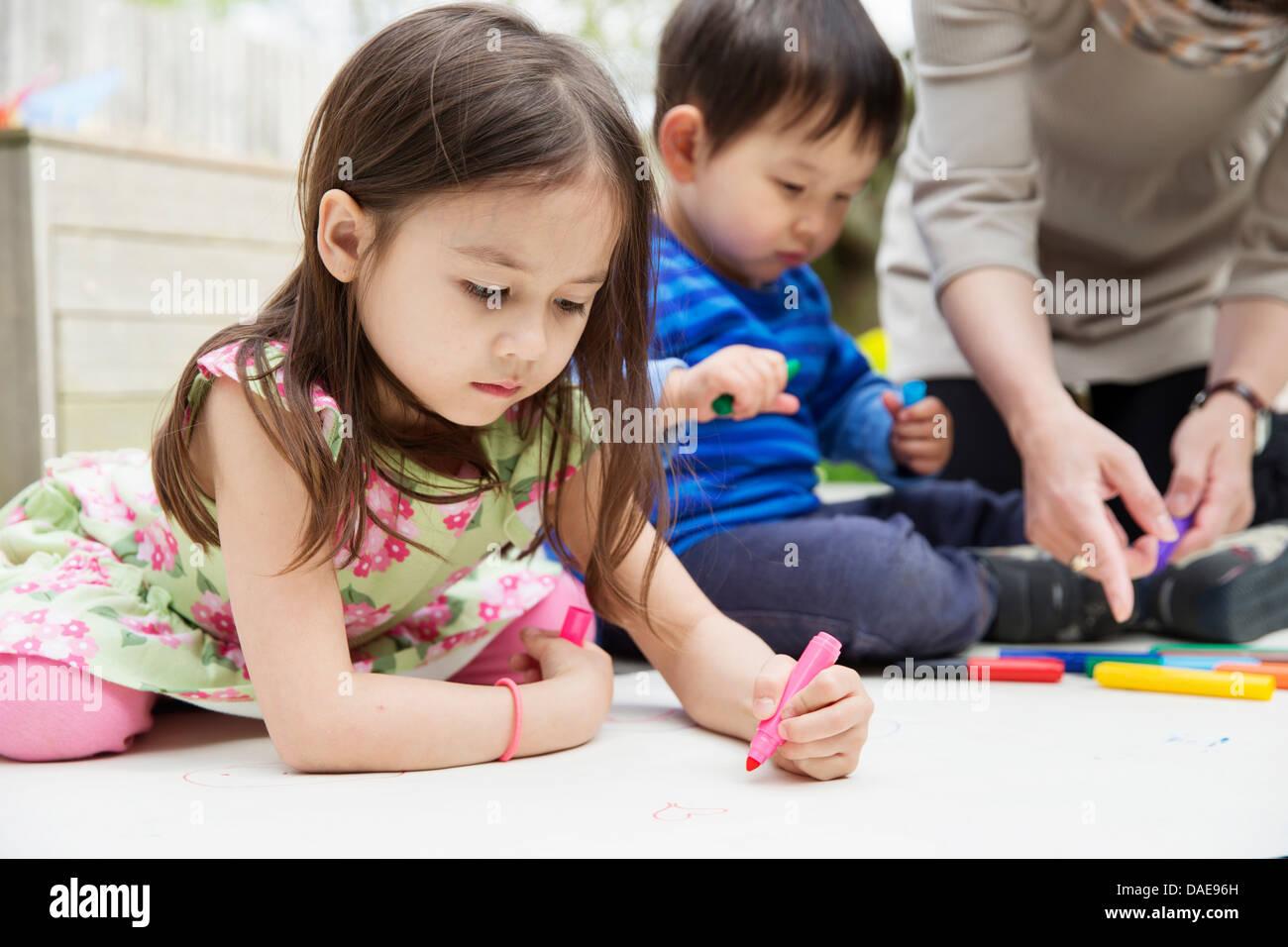 La madre y dos hijos en el jardín de dibujo Foto de stock
