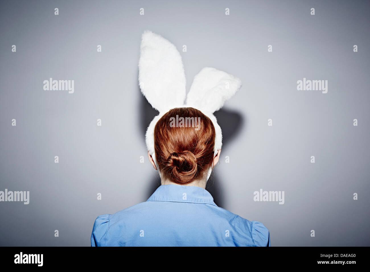 Vista posterior de la joven mujer vistiendo orejas de conejo Imagen De Stock