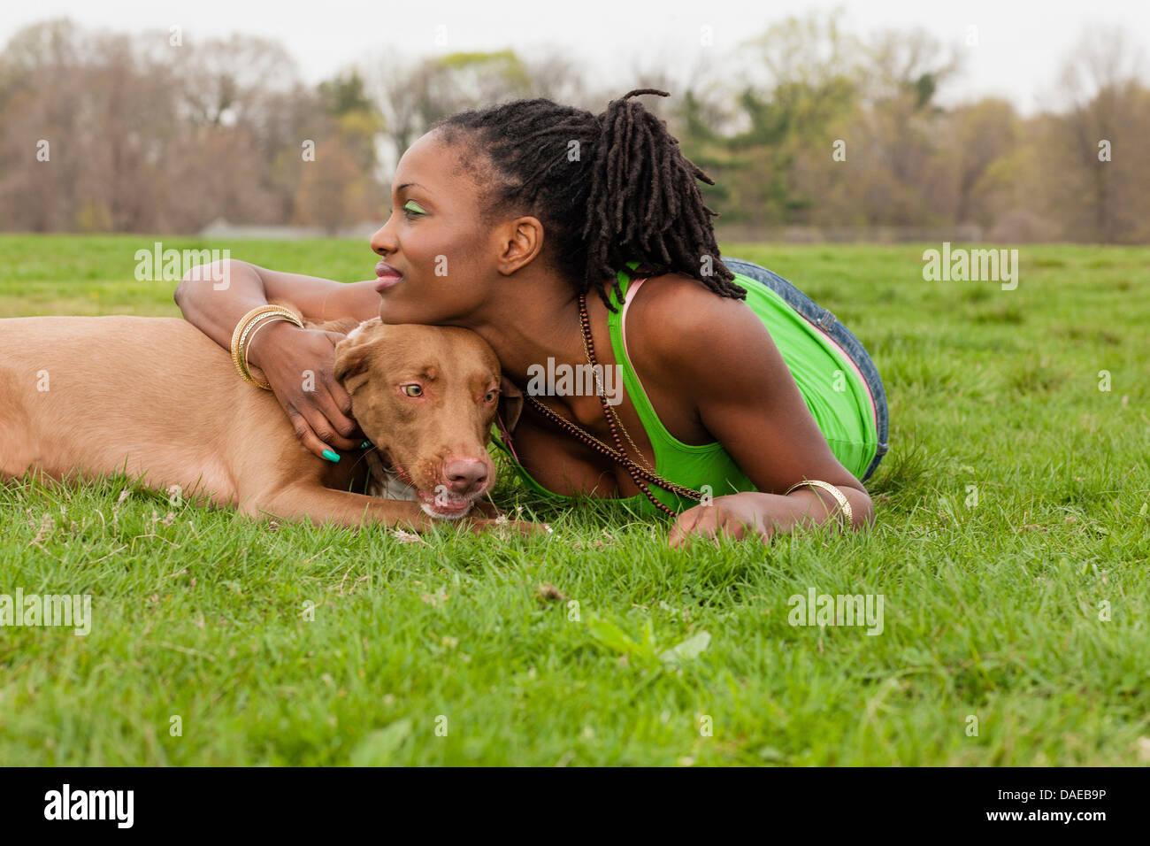 Mujer joven y su perro tumbado sobre el césped Imagen De Stock
