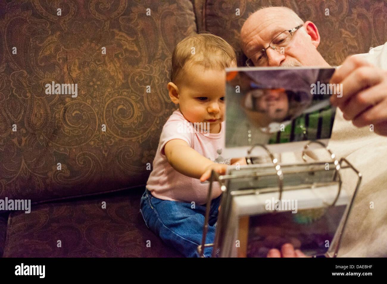 Abuelo y nieta de bebé mirando el álbum de fotos Imagen De Stock