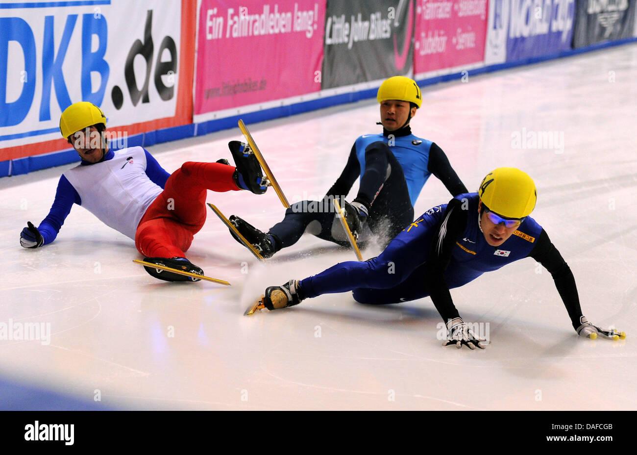 Im Herren-Finale über die 500 metros stürzen am Samstag (19.02.2011) en der Eishalle en Dresden im Rahmen des Weltcup-Finales im Shorttrack Frankreichs Teobaldo Fauconnet (l), der US-Amerikaner Simon Cho (M) sowie der Südkoreaner Byeong-Jun Kim auf der Ziellinie, Fauconnet wurde später als Sieger vor Cho gewertet, Kim wurde disqualifiziert. Un diesem Wochenende trifft sich die Weltel Foto de stock