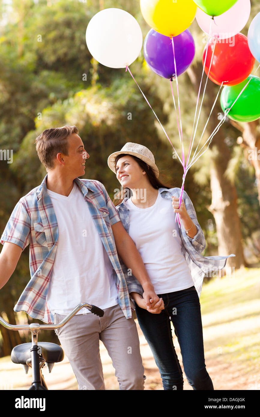 Linda pareja de adolescentes caminando por el parque cogidos de la mano Foto de stock