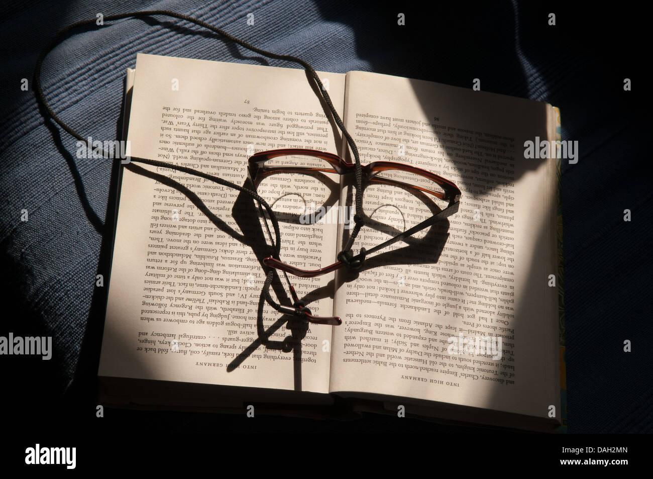 Gafas de un libro en un rayo de luz. Imagen De Stock