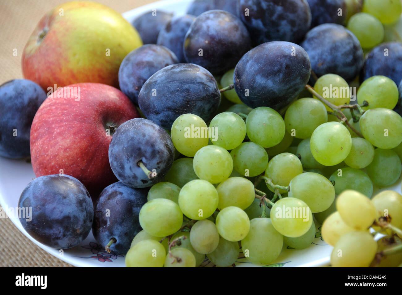 Las ciruelas, manzanas y uvas en una placa Imagen De Stock