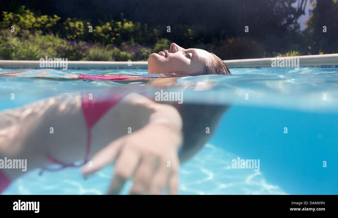 Mujer flotando en la piscina Foto de stock