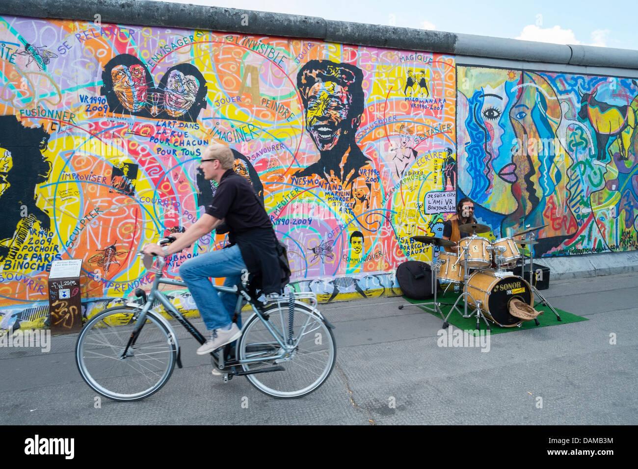 Músico busking en la calle junto al Muro de Berlín en el East Side Gallery en Berlín, Alemania Imagen De Stock