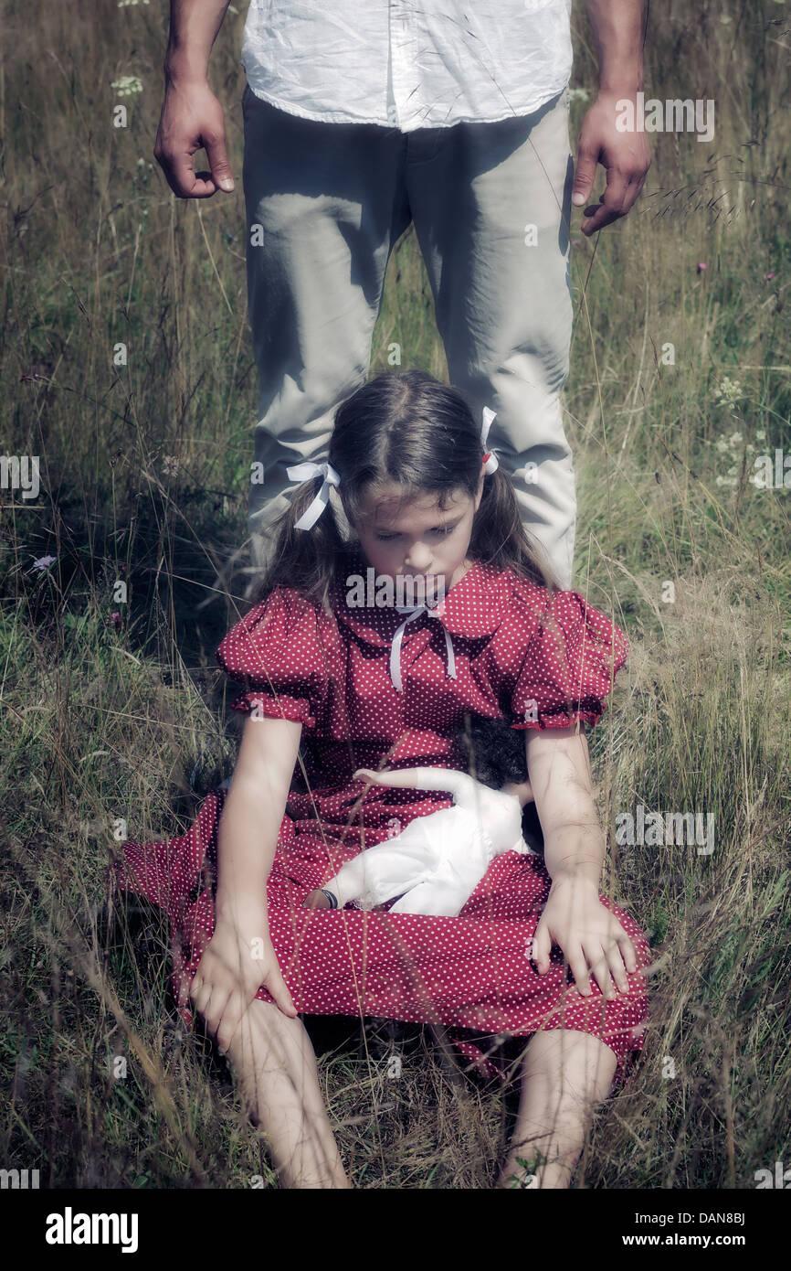 Una triste chica sentada en un campo, un hombre está de pie detrás de ella Imagen De Stock