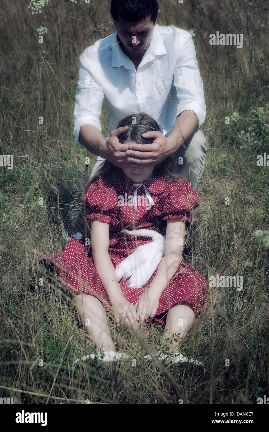 Una chica está sentada en el pasto, un hombre sostiene sus manos delante de sus ojos Imagen De Stock