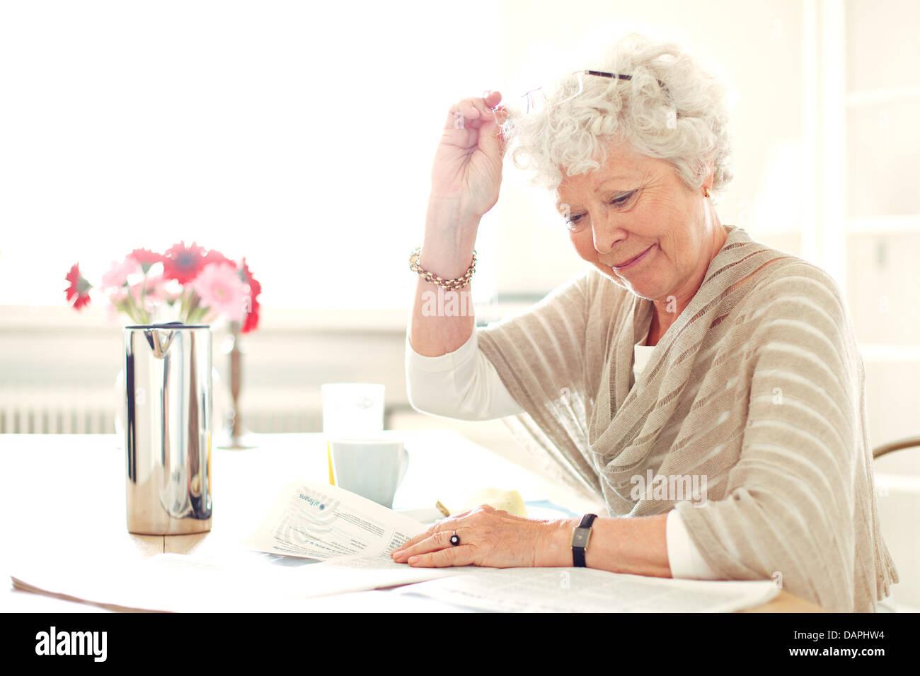 La abuela en casa ocupado leyendo algo Imagen De Stock