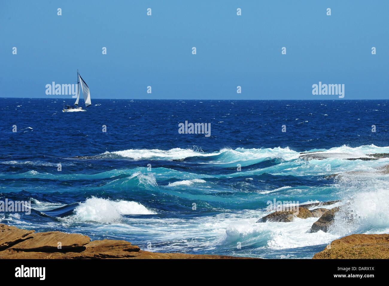 Yate en la costa con mar gruesa Foto de stock
