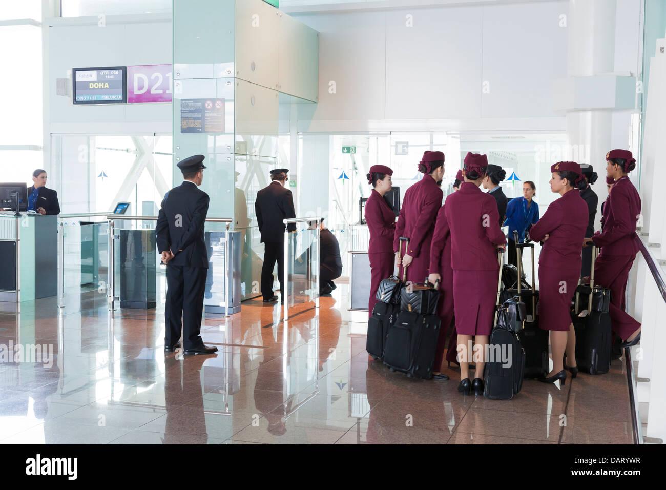 Qatar Airways pilotos y personal de cabina esperando en la puerta de salida en el aeropuerto. Imagen De Stock