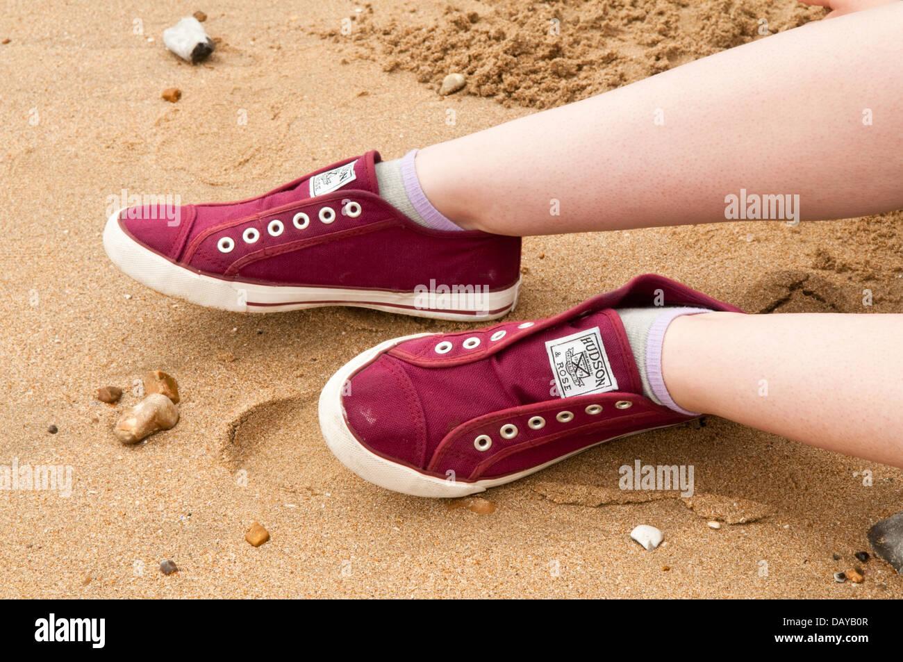 Un par de rojo oscuro laceless zapatillas sobre las piernas de una joven mujer en una playa de arena Foto de stock