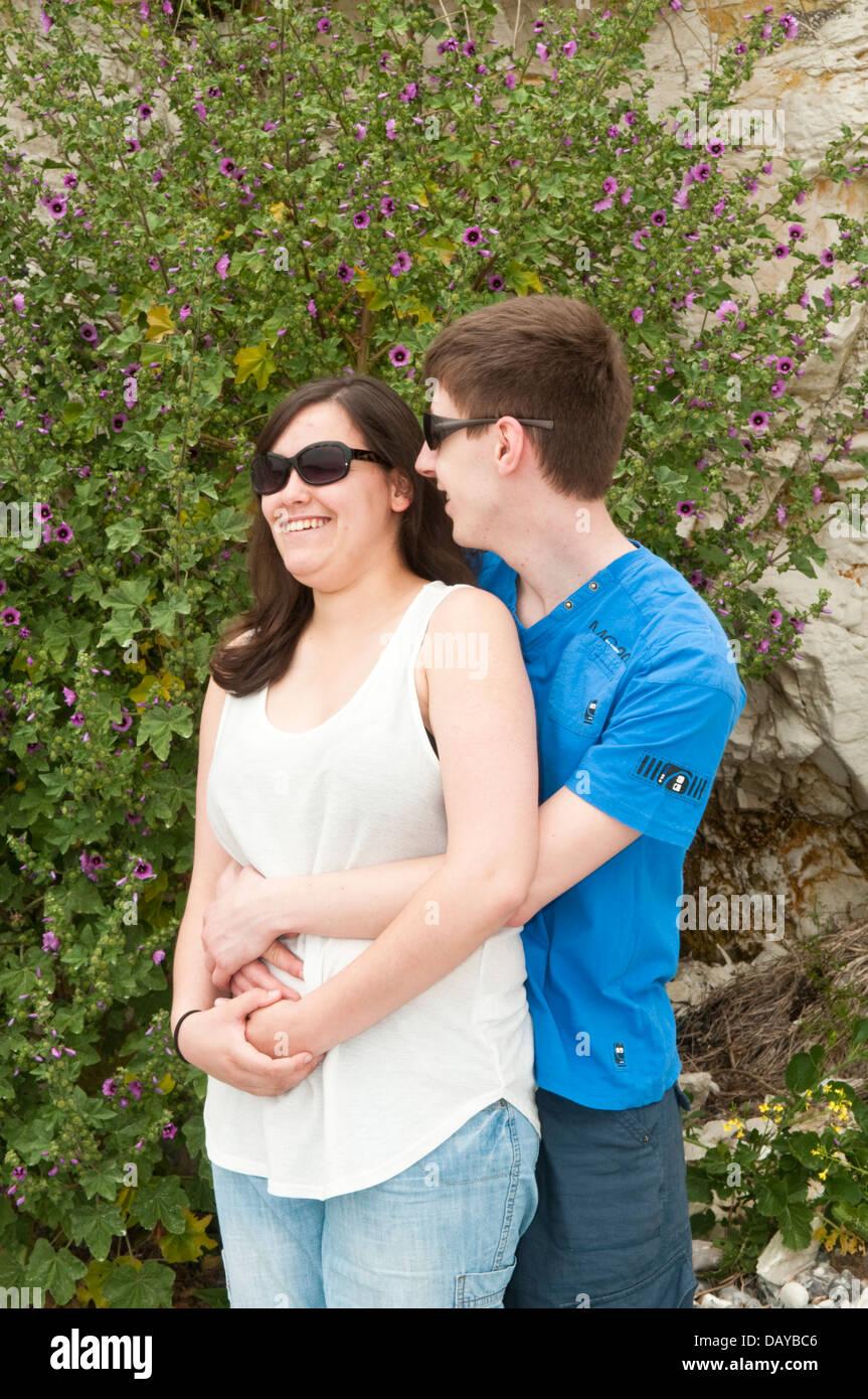 Una joven pareja relajada en su adolescencia o principios del veinte vistiendo ropa y gafas de sol Imagen De Stock