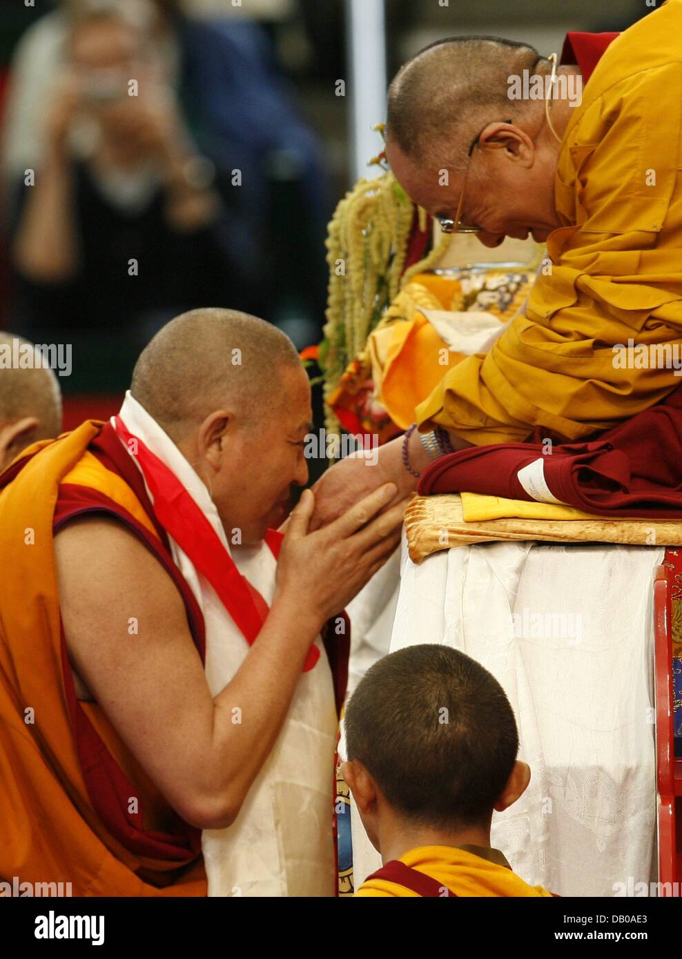 Un monje se pone en contacto con el Dalai Lama (R) en el trono en Hamburgo, Alemania, el 27 de julio de 2007. LosFoto de stock