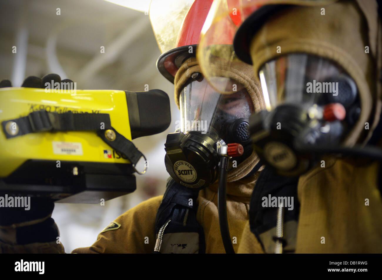 Técnico de Mantenimiento de casco de 3ª clase Timothy Dunkel utiliza una imagen térmica durante un taladro de lucha contra incendios a bordo del buque anfibio un Foto de stock