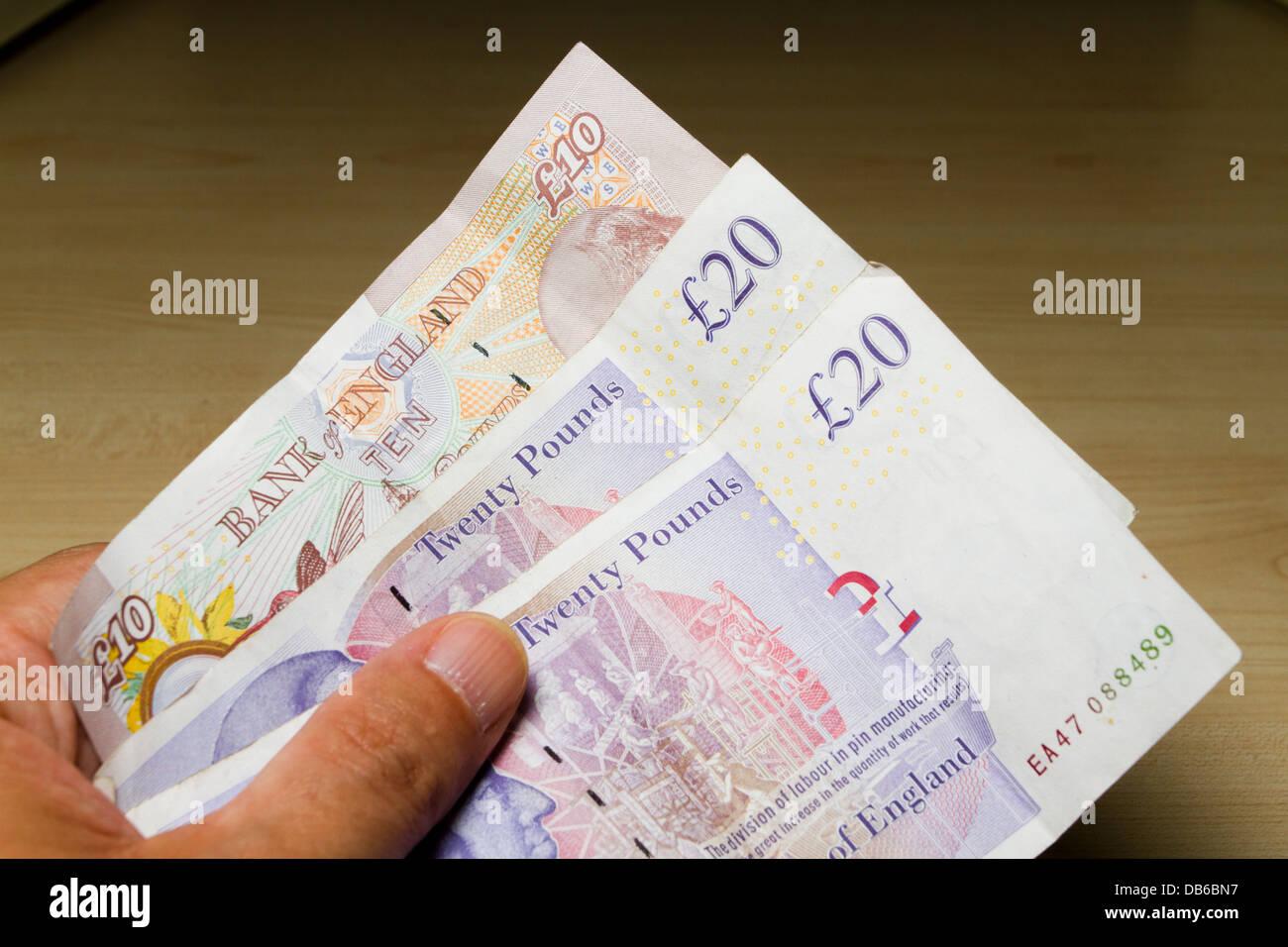 Mantenga la mano de un hombre de 50 libras esterlinas en efectivo, compuesto de 2 £20 £10 libras y 1 notas, Imagen De Stock