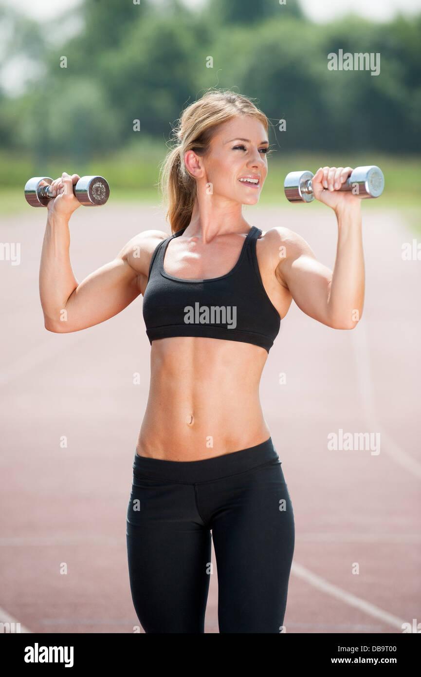 Mujer que hacen ejercicio al aire libre una rutina con pesas Imagen De Stock