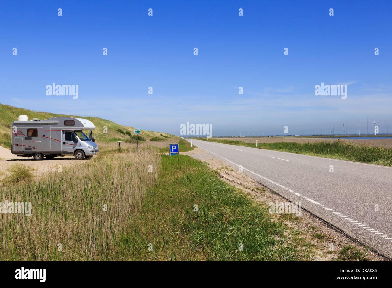 Autocaravana aparcada por una duna de arena junto a la carretera de la costa 181 sobre Bovling Klit istmo con vistas Bovling Fjord en el oeste de Jutlandia, Dinamarca Foto de stock