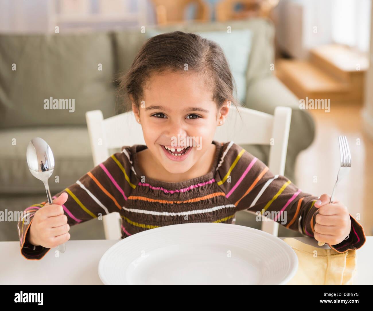 Chica hispana pidiendo comida en la mesa Foto de stock