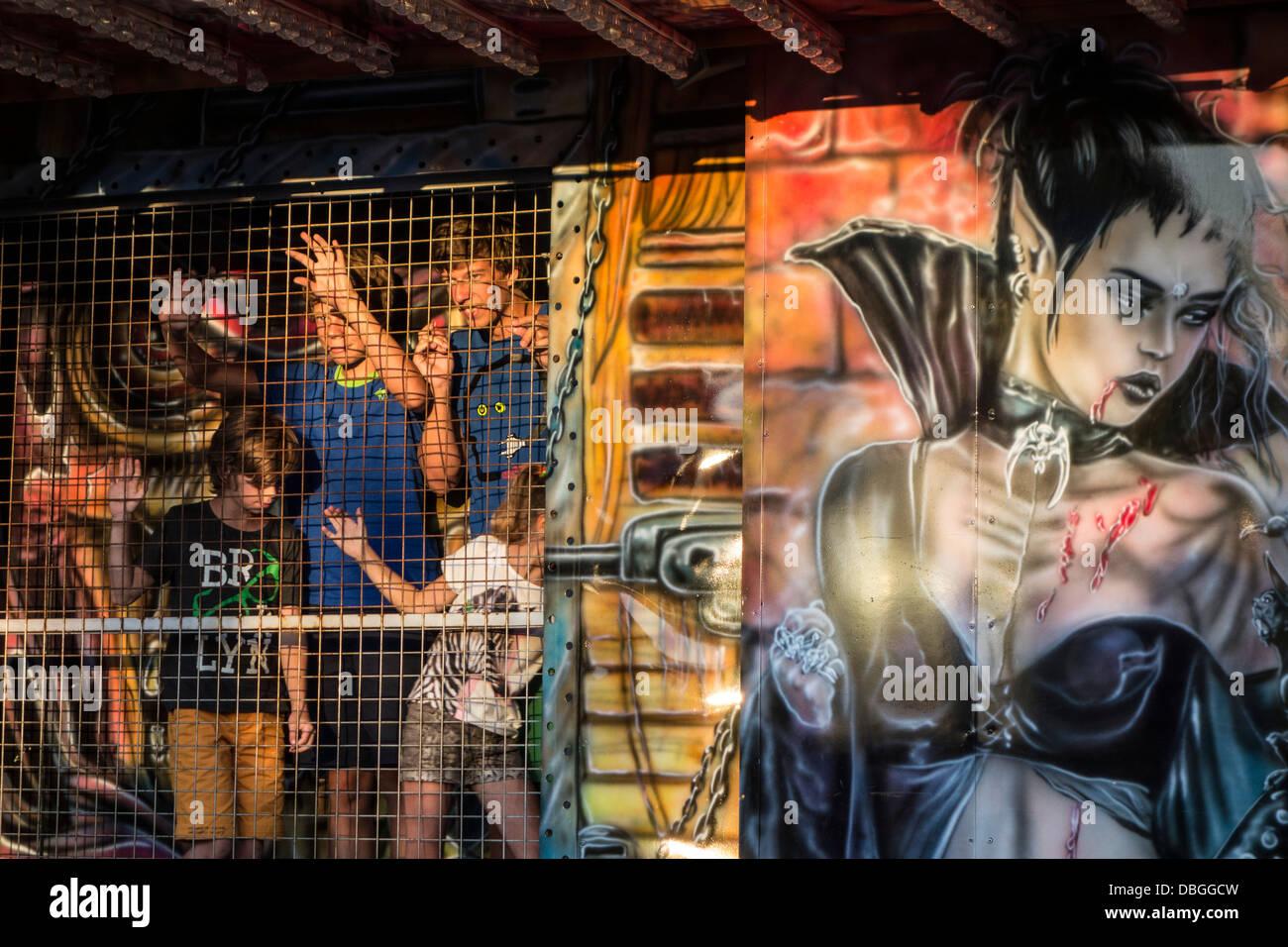 Niños en el recinto ferial atracción Haunted House en viajar feria / viajar fun fair Imagen De Stock