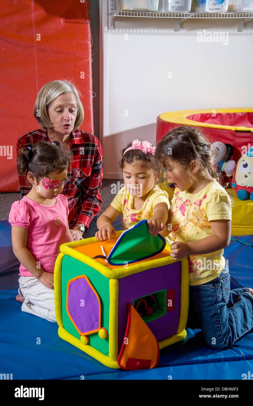 Excitado y parcialmente ciegos estudiantes ciegos encontrar regalos por tocar en un cubo acolchado en una clase Imagen De Stock