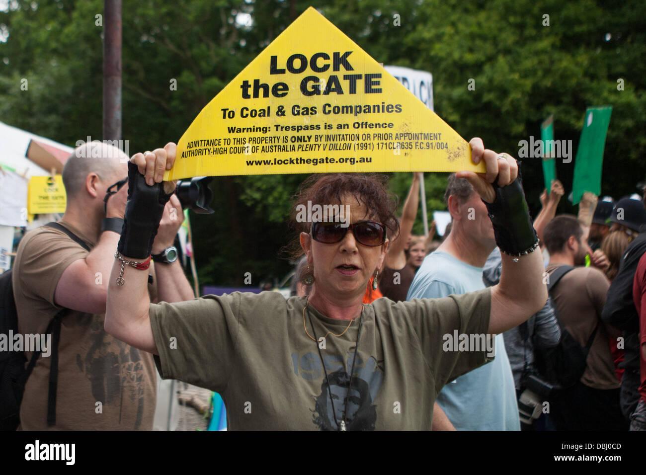 Balcombe, West Sussex, Reino Unido. El 31 de julio, 2013. Mujer sostiene aloft bloquear la puerta del letrero. Protesta contra la Cuadrilla de perforación y fracking justo en las afueras de la aldea de Balcombe en West Sussex. Balcombe, West Sussex, Reino Unido. Crédito: martyn wheatley/Alamy Live News Foto de stock