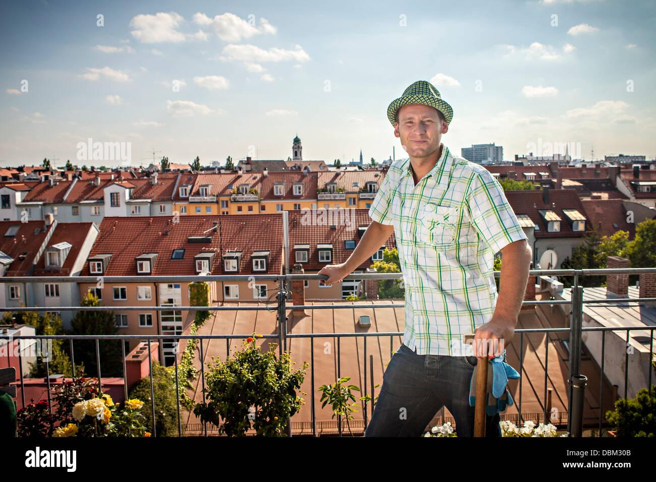 Hombre de pie en el balcón, Munich, Baviera, Alemania, Europa Imagen De Stock