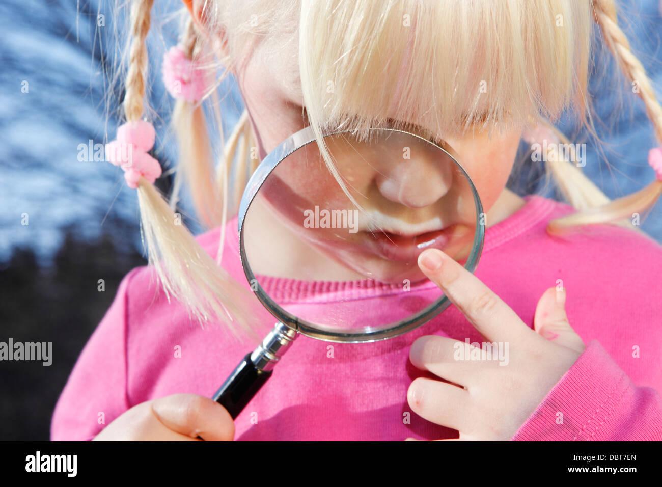 Chica (4-5) jugando con lupa Foto de stock