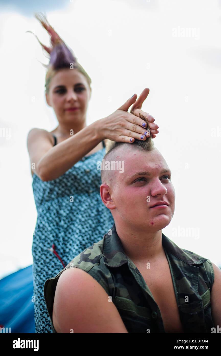 Un participante del festival obteniendo su corte de pelo punk realizada durante el festival de música Woodstock Imagen De Stock