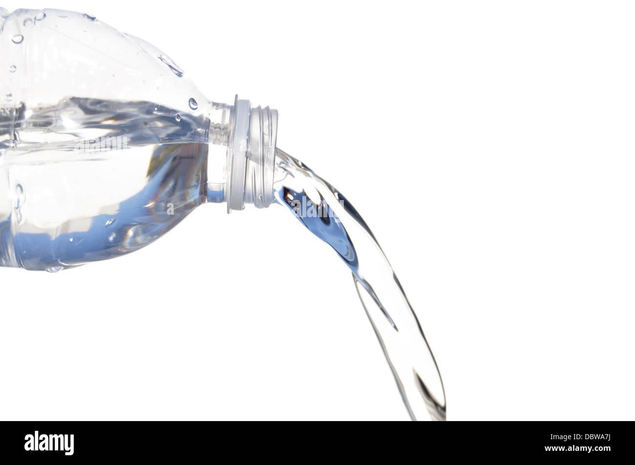 Vertido del agua de botella de plástico aislado en blanco Imagen De Stock