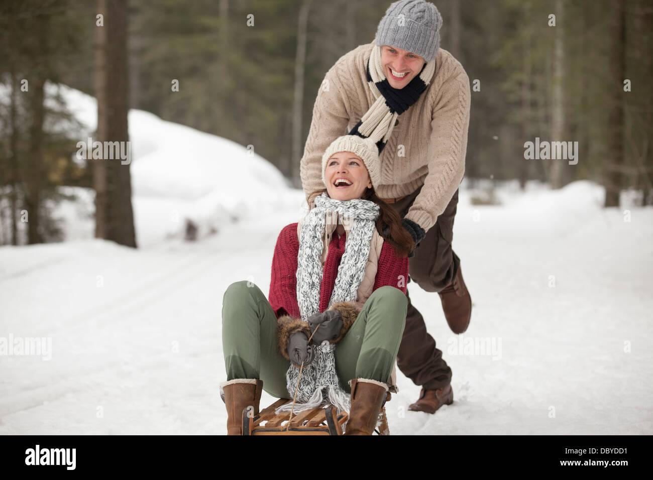 Feliz pareja de trineo en campo nevado Foto de stock