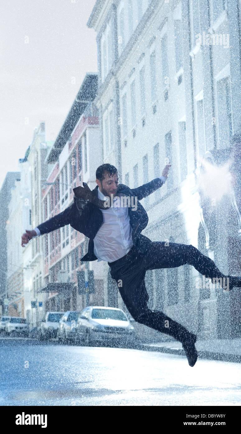 Empresario bailando en la calle lluviosa Foto de stock