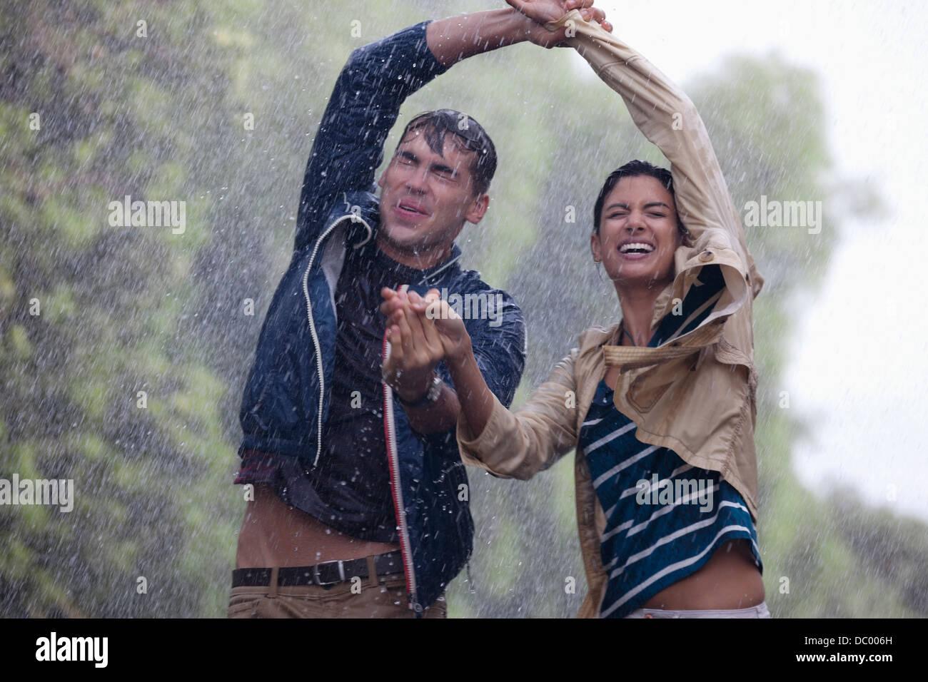 Feliz pareja bailando en la lluvia Imagen De Stock