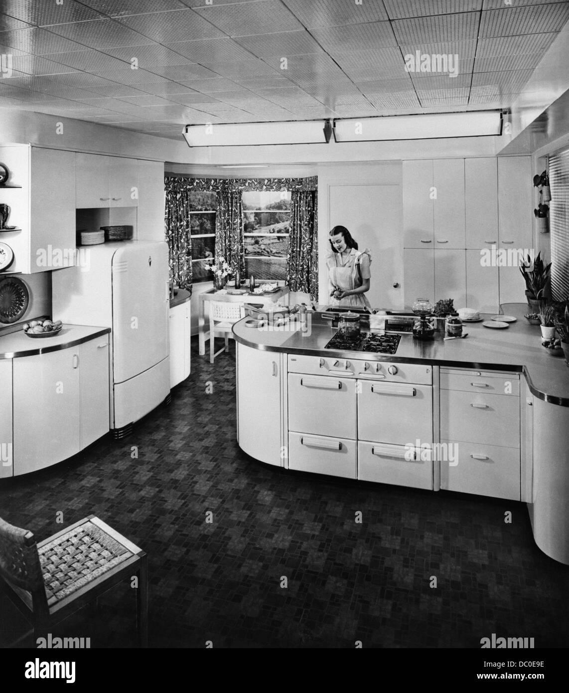 Ama de casa de 1950 trabajando en la moderna cocina eléctrica Foto de stock