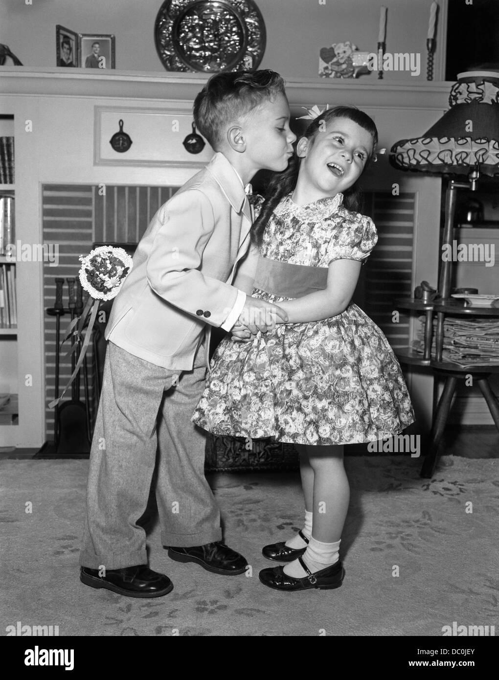 J1950s Little Boy en traje y corbata INTENTANDO BESO niña vestido de fiesta Imagen De Stock