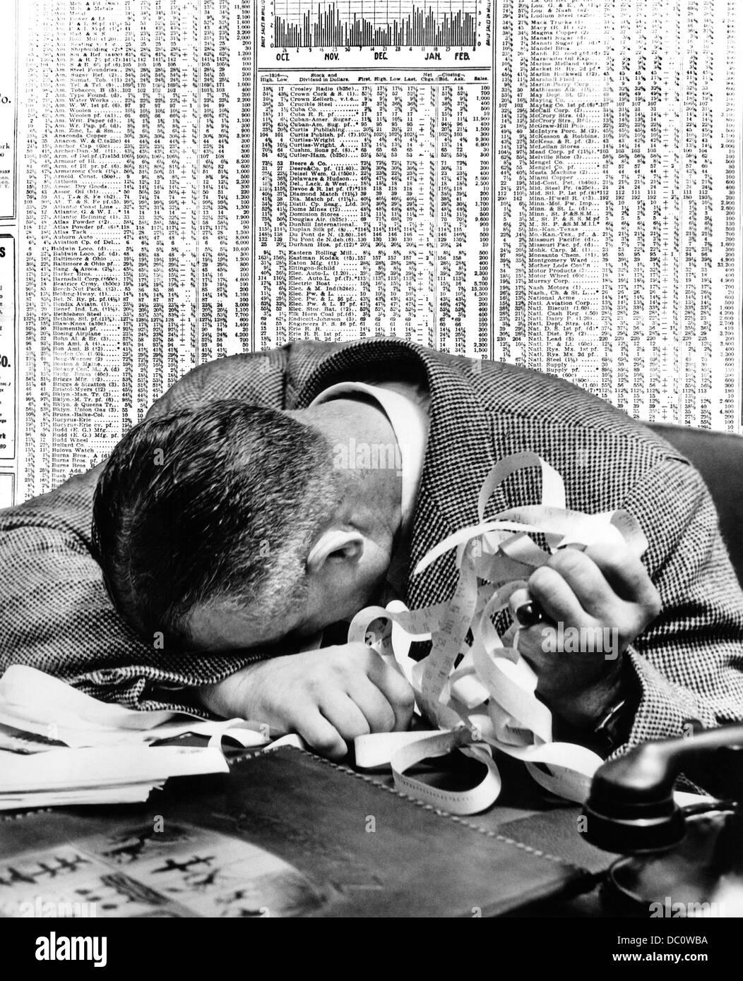 1940 El hombre la cabeza apoyada en la mesa mantiene Stock Ticker tape con periódico STOCK página detrás Imagen De Stock