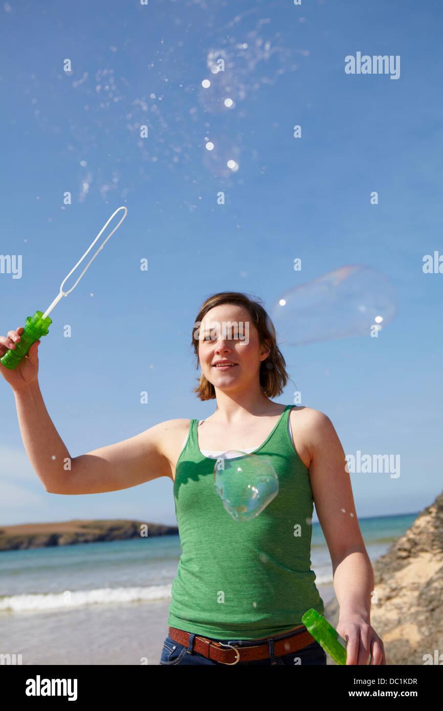 Mujer joven en la costa jugando con la varita de la burbuja Imagen De Stock