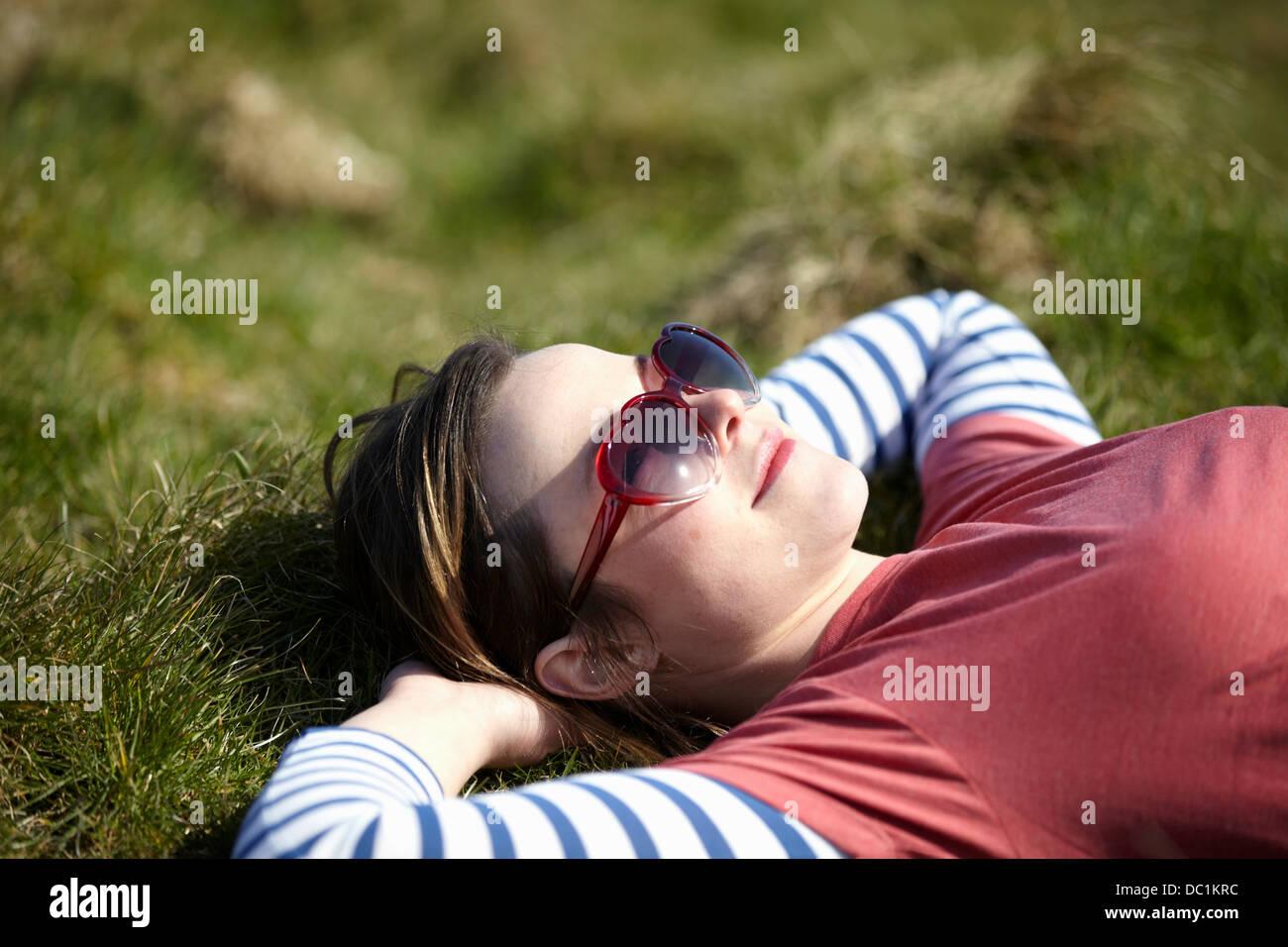 Mujer joven llevaba gafas de sol con forma de corazón recostado sobre el césped Imagen De Stock