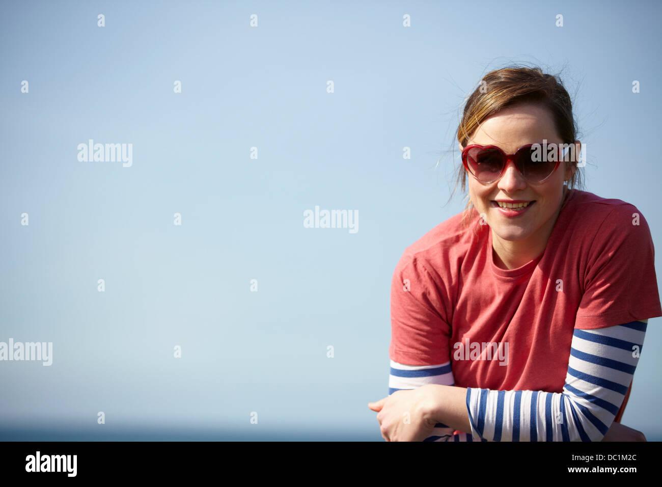 Retrato de mujer joven llevaba gafas de sol con forma de corazón en la costa Imagen De Stock