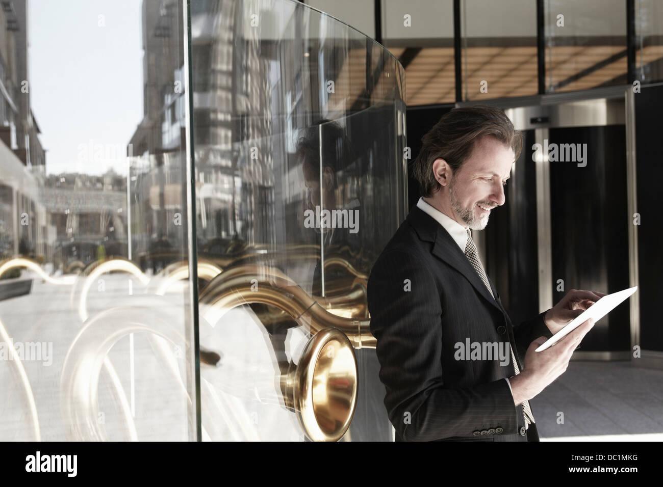 Adulto medio empresario apoyado contra la ventana de guardar y usar tableta digital Imagen De Stock