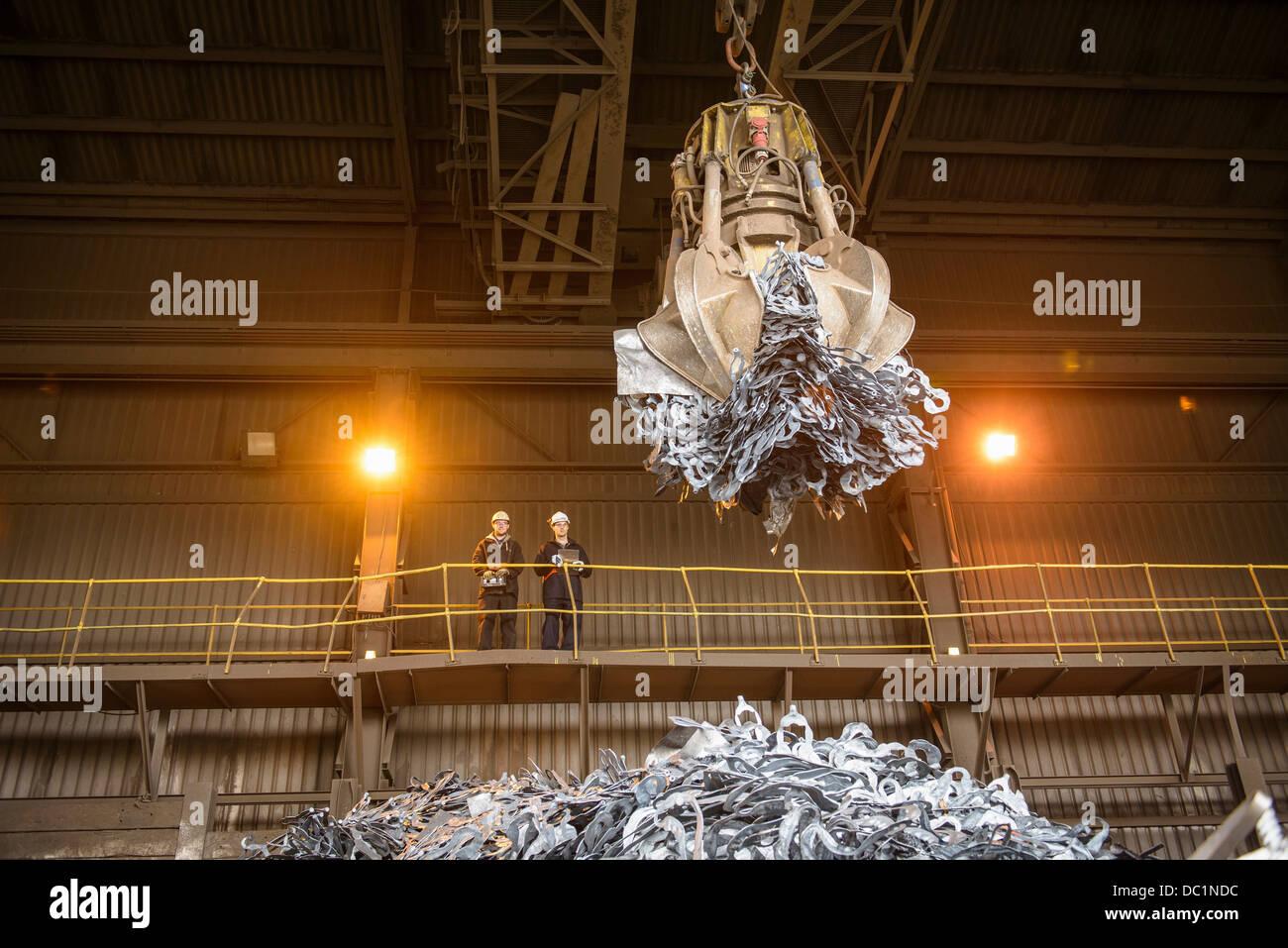 Los trabajadores siderúrgicos viendo pinza mecánica en fundición de acero Foto de stock