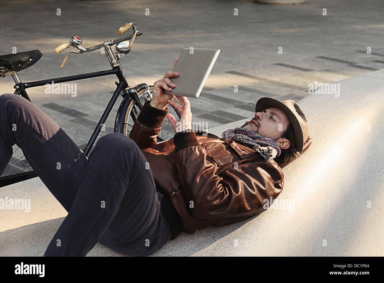 Mitad hombre adulto tumbado sobre la espalda con tableta digital Imagen De Stock