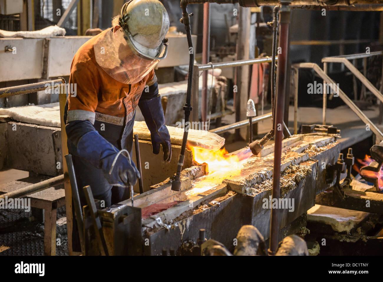 Trabajador probar el metal fundido en la planta de reciclaje de aluminio Imagen De Stock