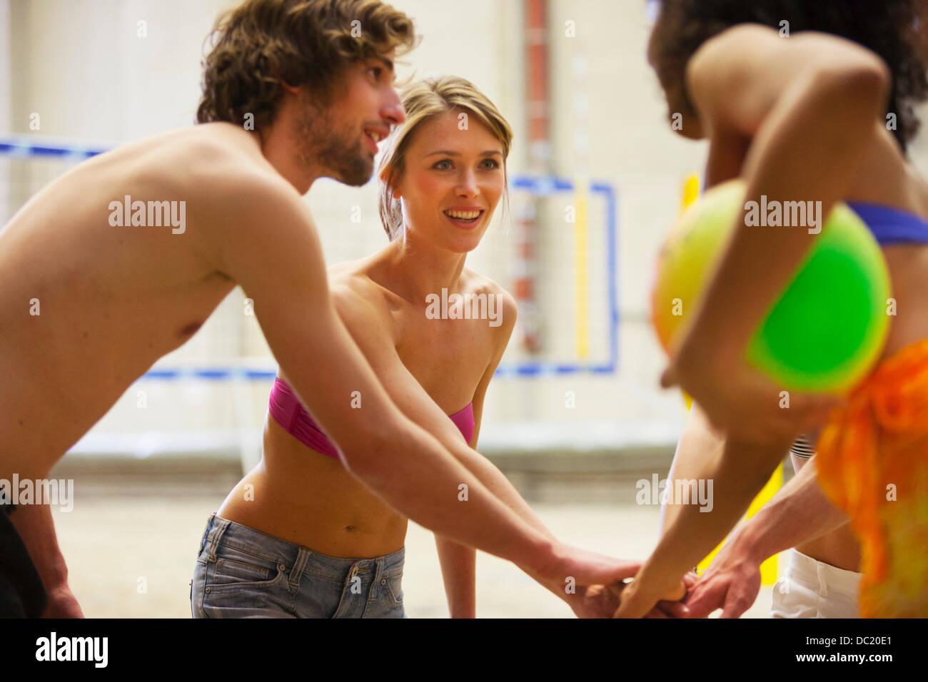Amigos que hablen al interior del equipo de voleibol de playa Imagen De Stock