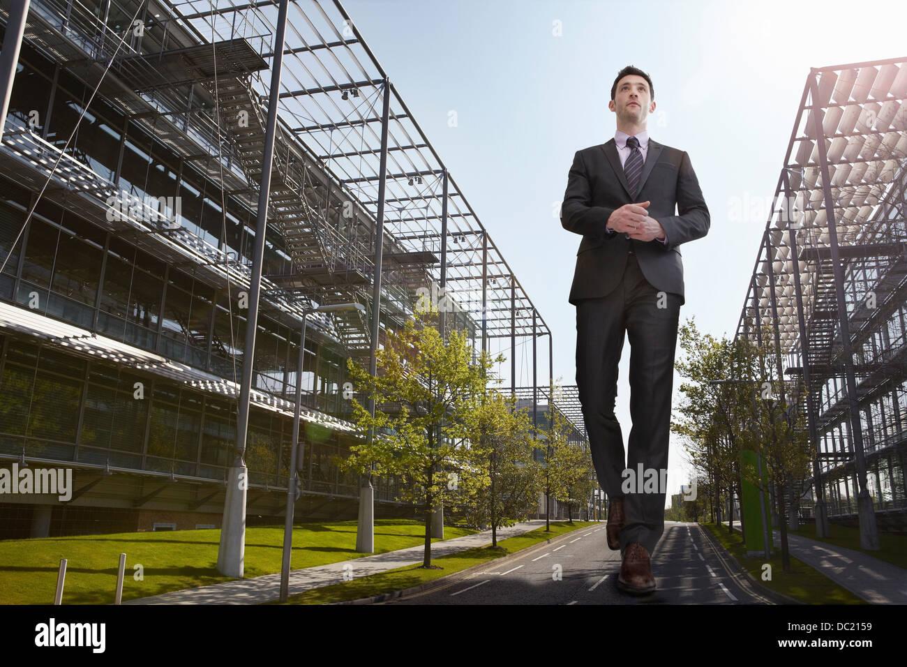 Empresario sobredimensionado caminando en carretera, vista de ángulo bajo Imagen De Stock