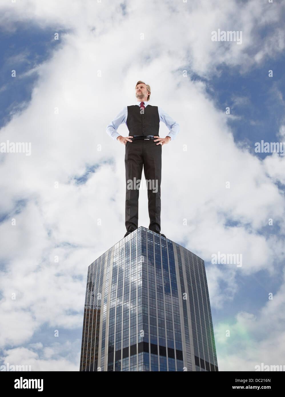 Empresario sobredimensionado de pie en rascacielos, bajo ángulo de visión Imagen De Stock